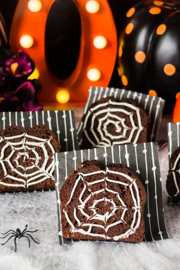 chocolate bread decorated with frosting spiderwebs on top on black and white napkins