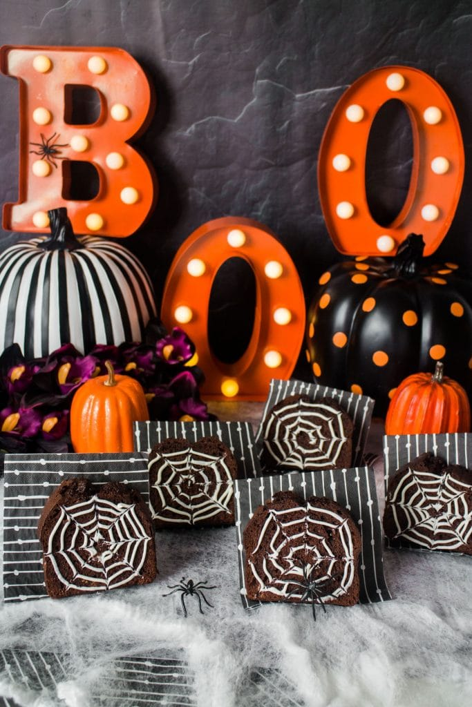 chocolate bread with frosting spider webs in front of halloween decorations
