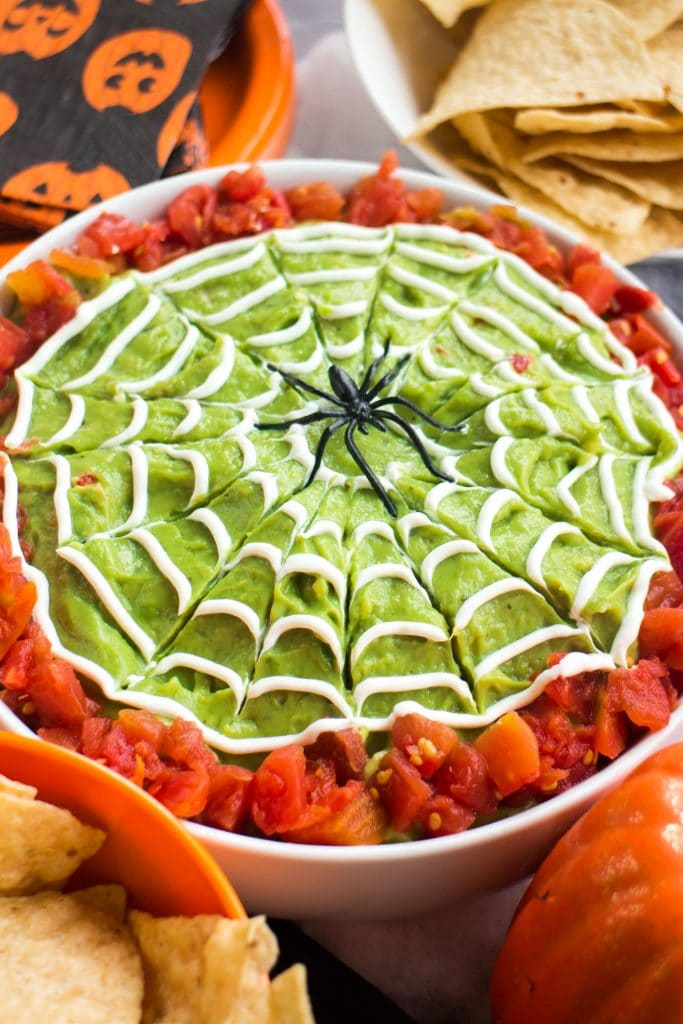 bowl of guacamole with diced tomatoes and spider decoration on top