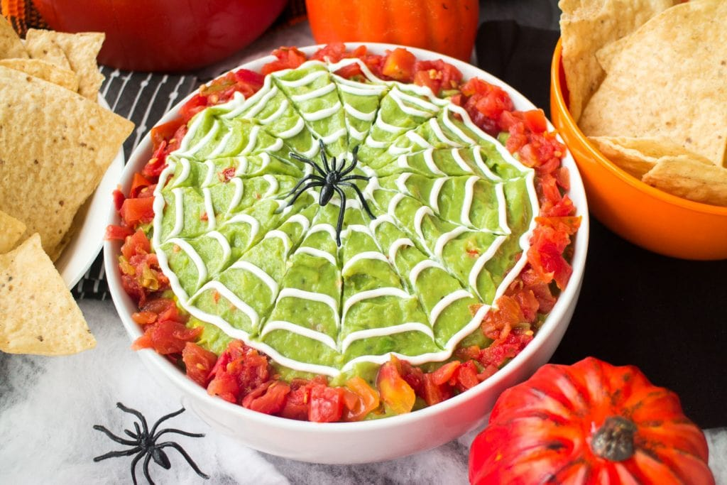 bowl of guacamole on halloween decorated table with tortilla chips