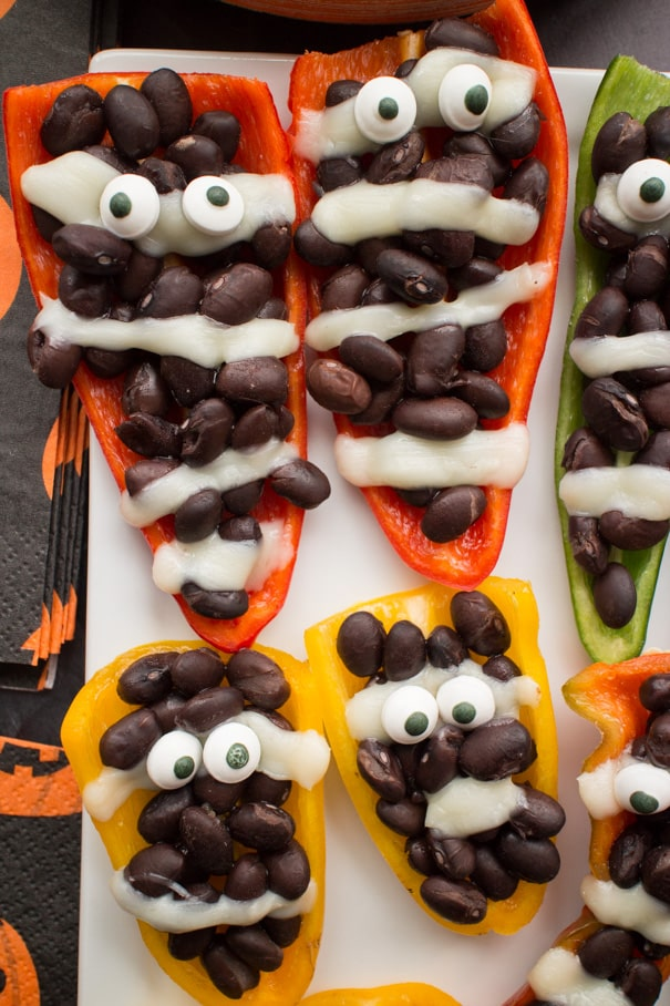 EASY Halloween Stuffed Mummy Peppers recipe for parties and kids!  These mummies only require 3 ingredients and make the cutest appetizer for a party!  This is one of my favorite Halloween food ideas!