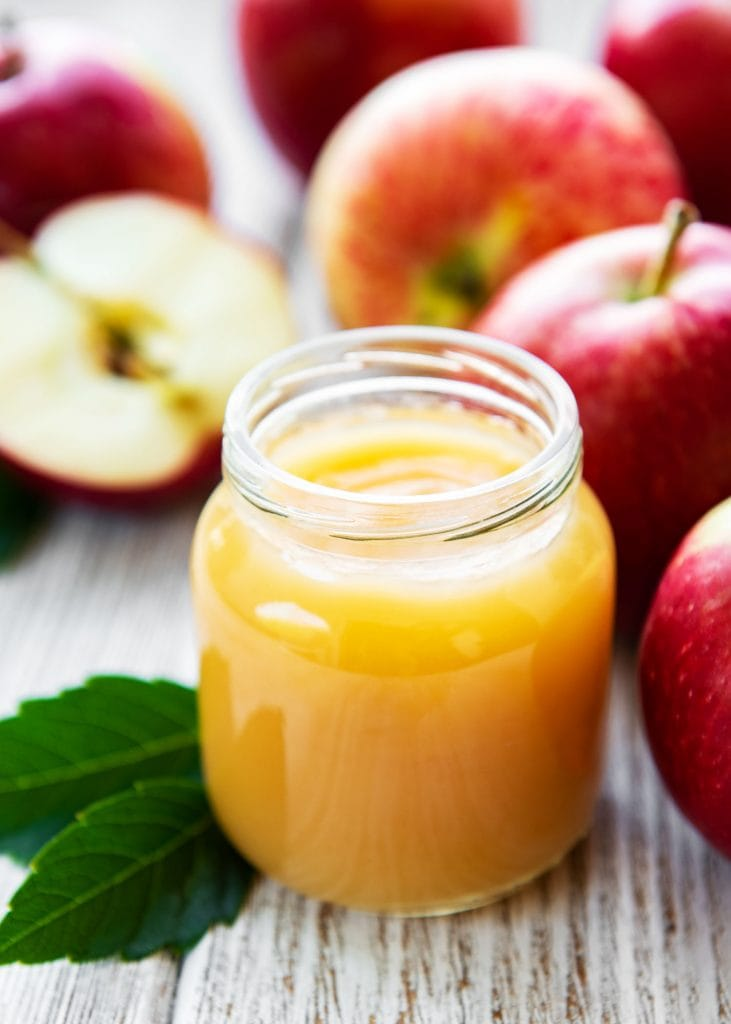applesauce in glass jar with red apples in background