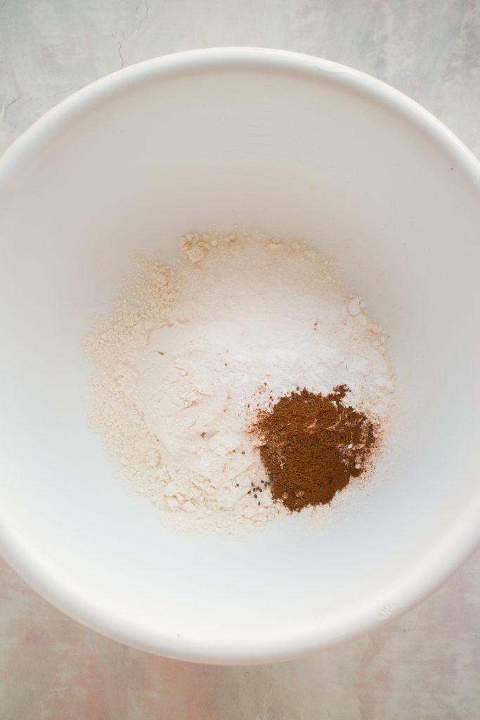 flour, sugar, baking powder, baking soda, salt and cinnamon in bowl.