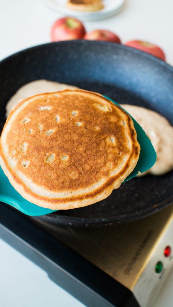pancake being flipped in frying pan.