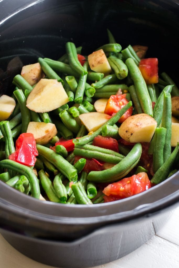 fresh green beans, potatoes and tomatoes sitting in black crock pot