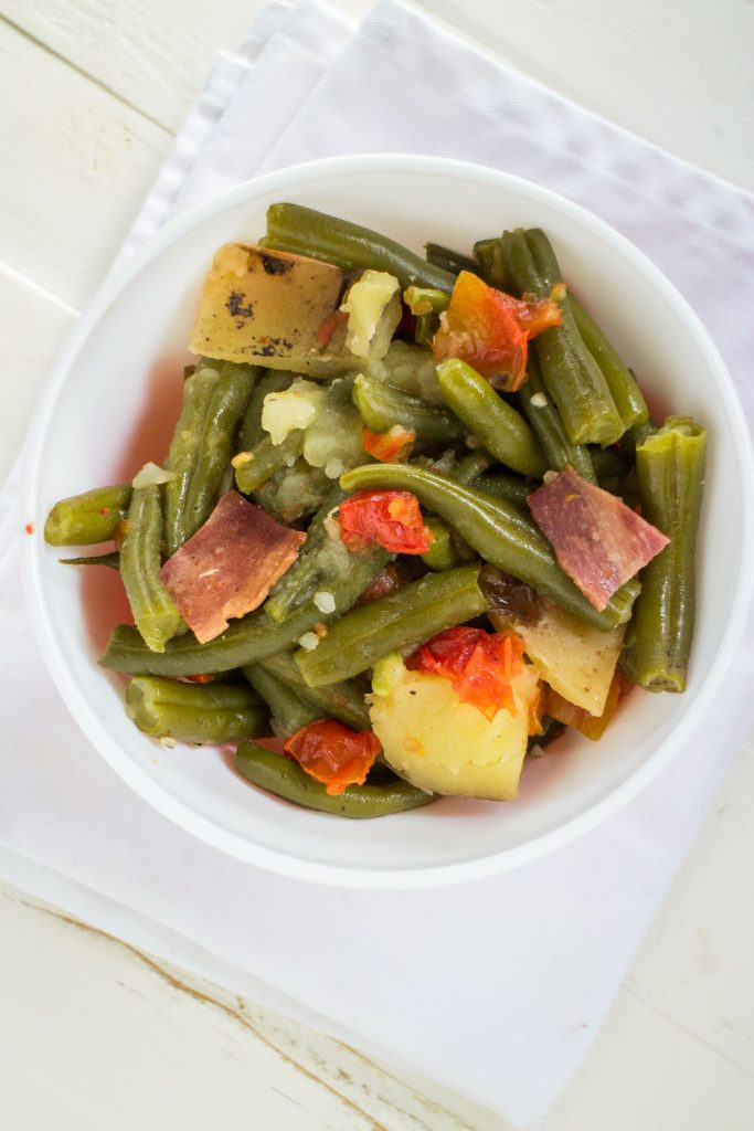 green beans and potatoes with bacon made in the slow cooker in white serving bowl