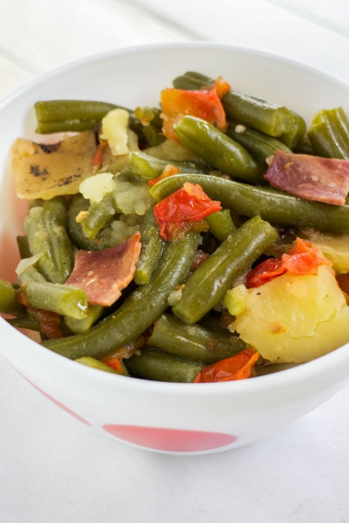 slow cooker green beans cooked tomatoes, potatoes and bacon in white serving bowl