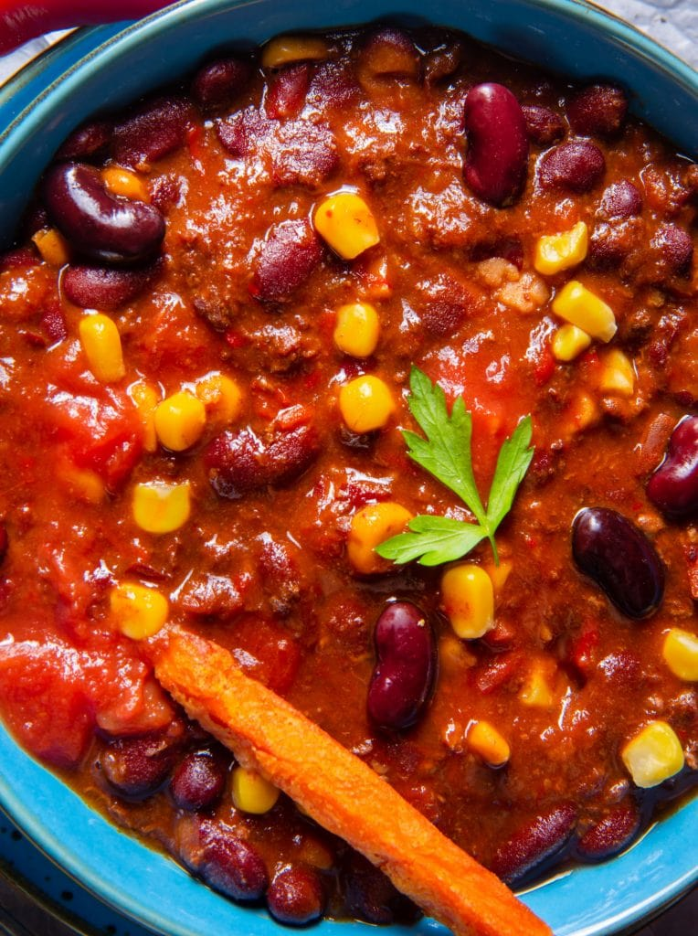 ground beef chili in blue bowl on table