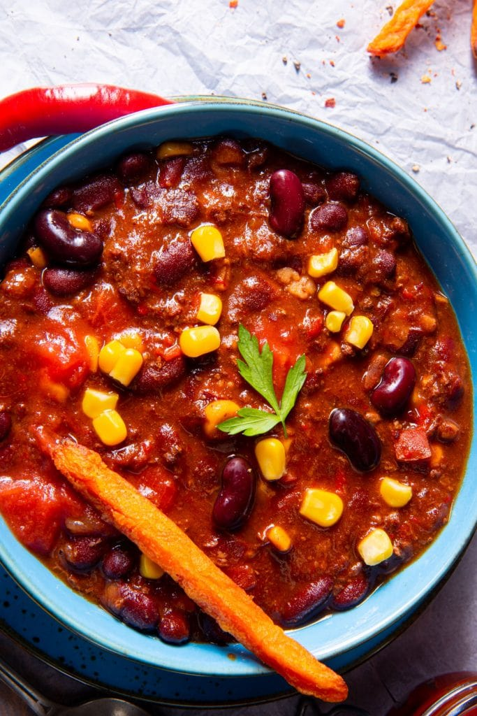 bowl of beef chili with sweet potato being dipped into it.