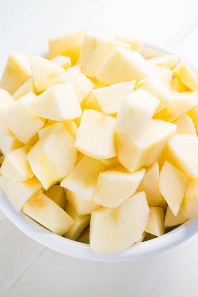 chopped up apples in white bowl