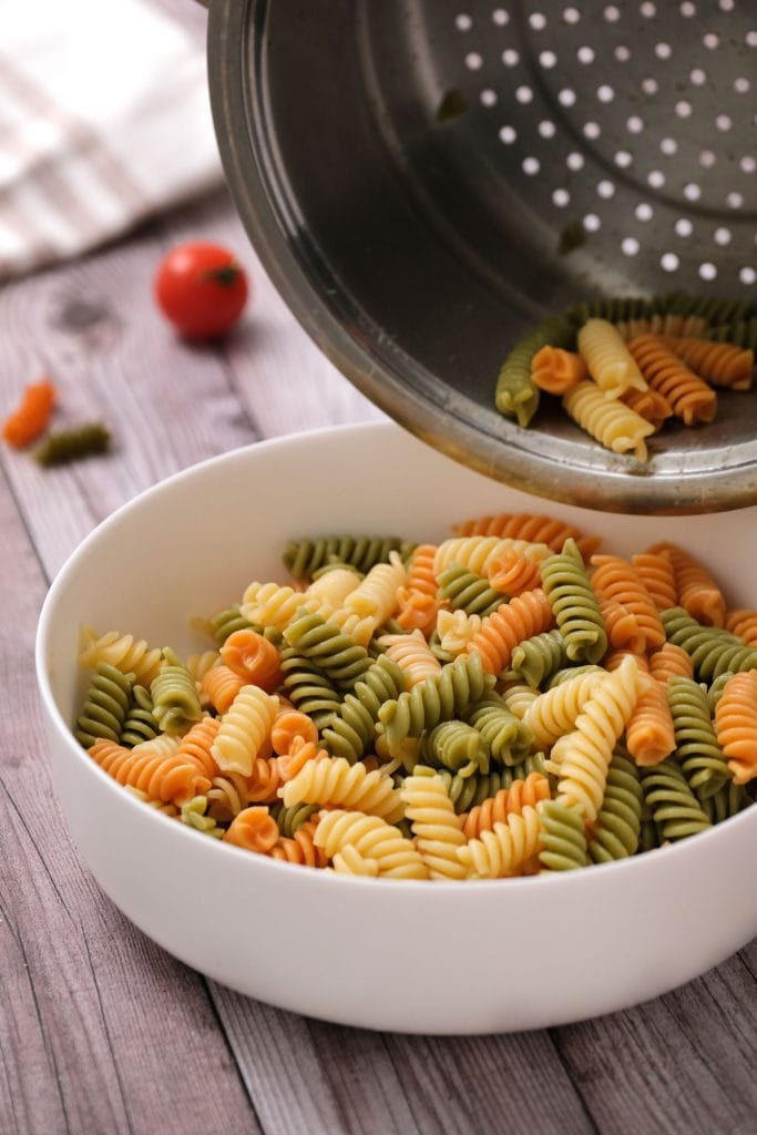 tri color rotini being drained into white bowl