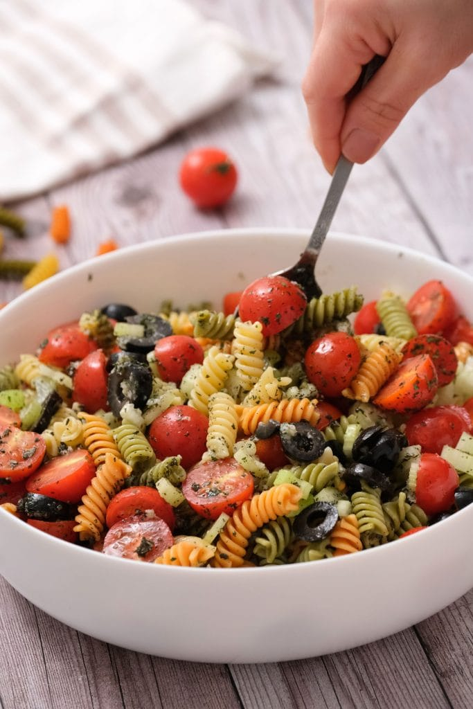 fork mixing pasta in white bowl with cherry tomatoes, olives and herbs