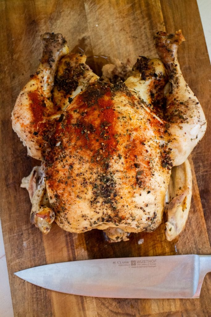 juicy whole chicken cooked in slow cooker sitting on cutting board