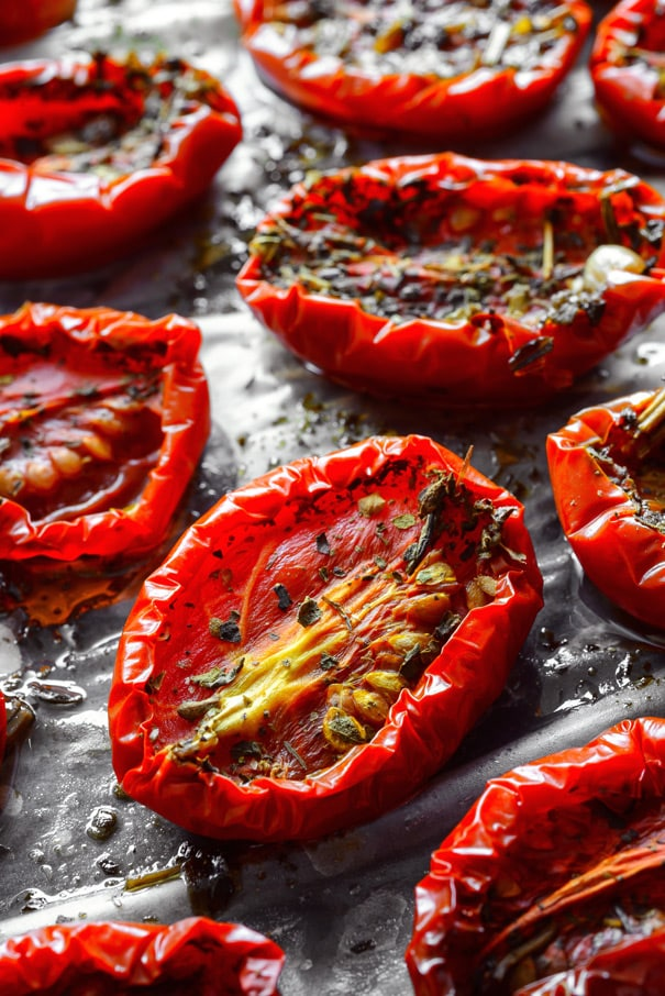 Oven Baked Sun-dried Tomatoes in olive oil and Italian spices recipe.  This easy homemade recipe will leave your kitchen smelling great and you saying MMMMMM! Includes directions on how to make and freeze sun-dried tomatoes. Use them in pasta, chicken, shrimp, bread, pizza, dip and so many other recipes!