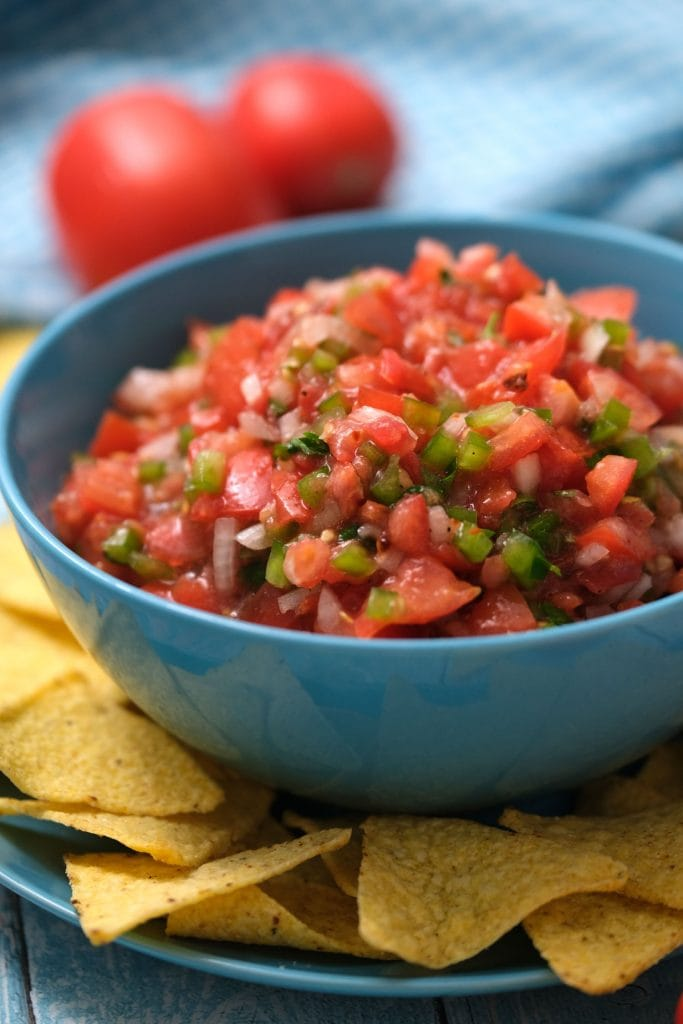 tomato salsa with green peppers and onions in blue bowl with tortilla chips