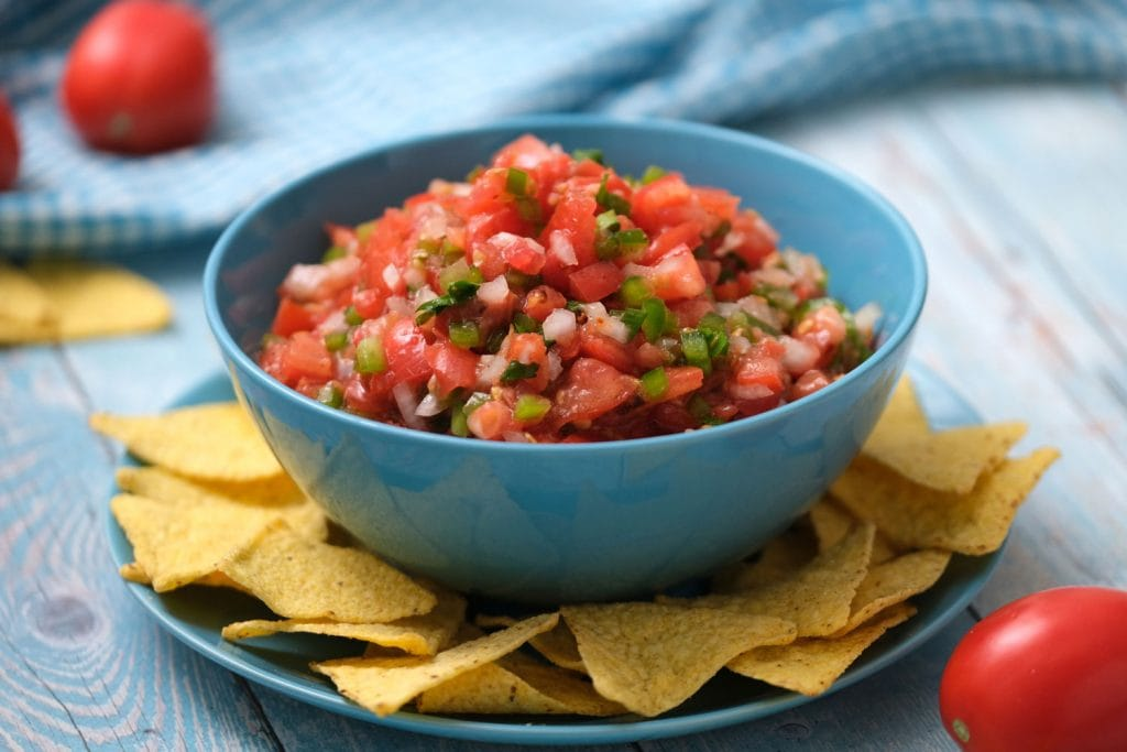 plate with bowl of salsa and corn tortilla chips