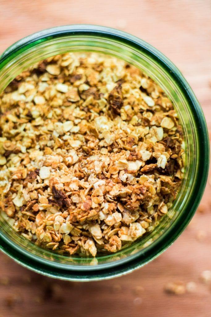 homemade granola in green mason jar on table.