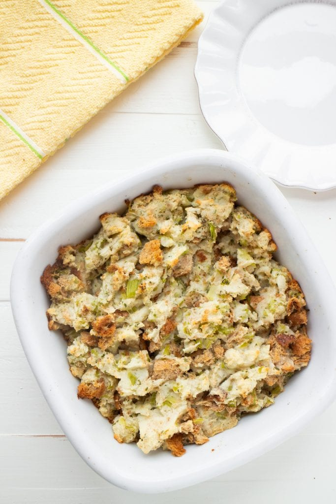 baked amish potato stuffing in baking dish on white table.