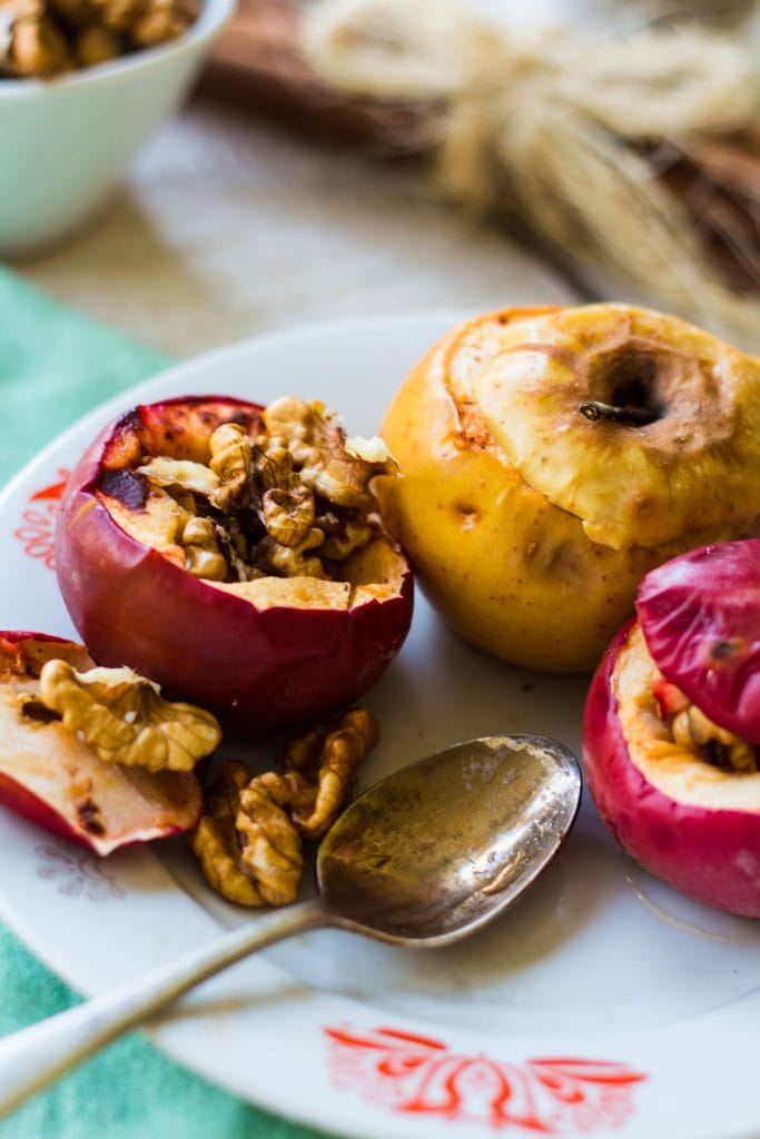 baked apples with pecans and walnuts on white plate