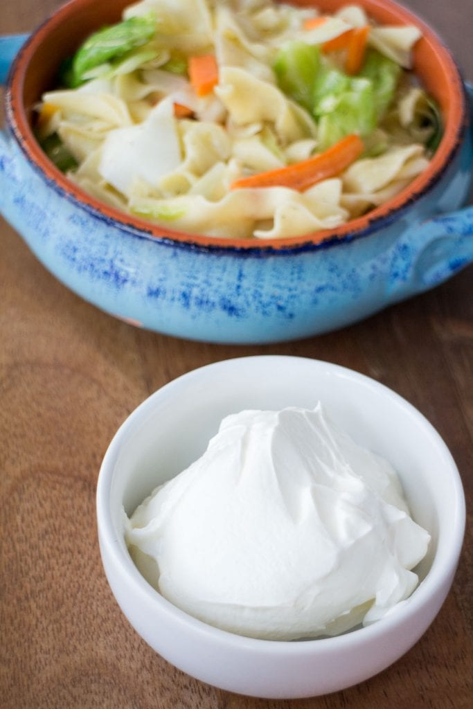 bowl of sour cream with bowl of cabbage and noodles in background