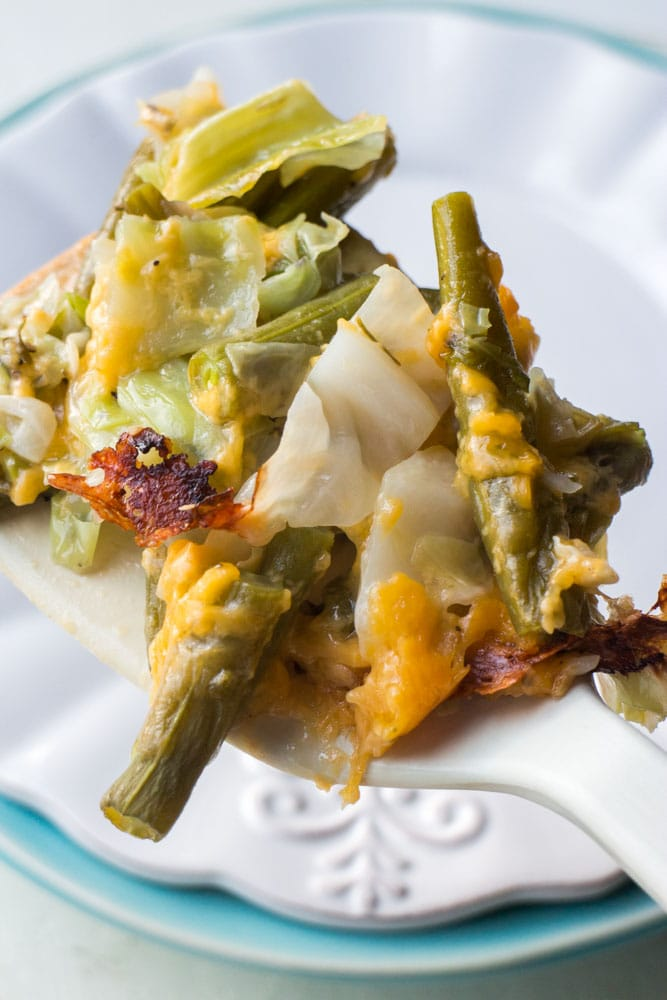 cheesy green beans on spoon being served