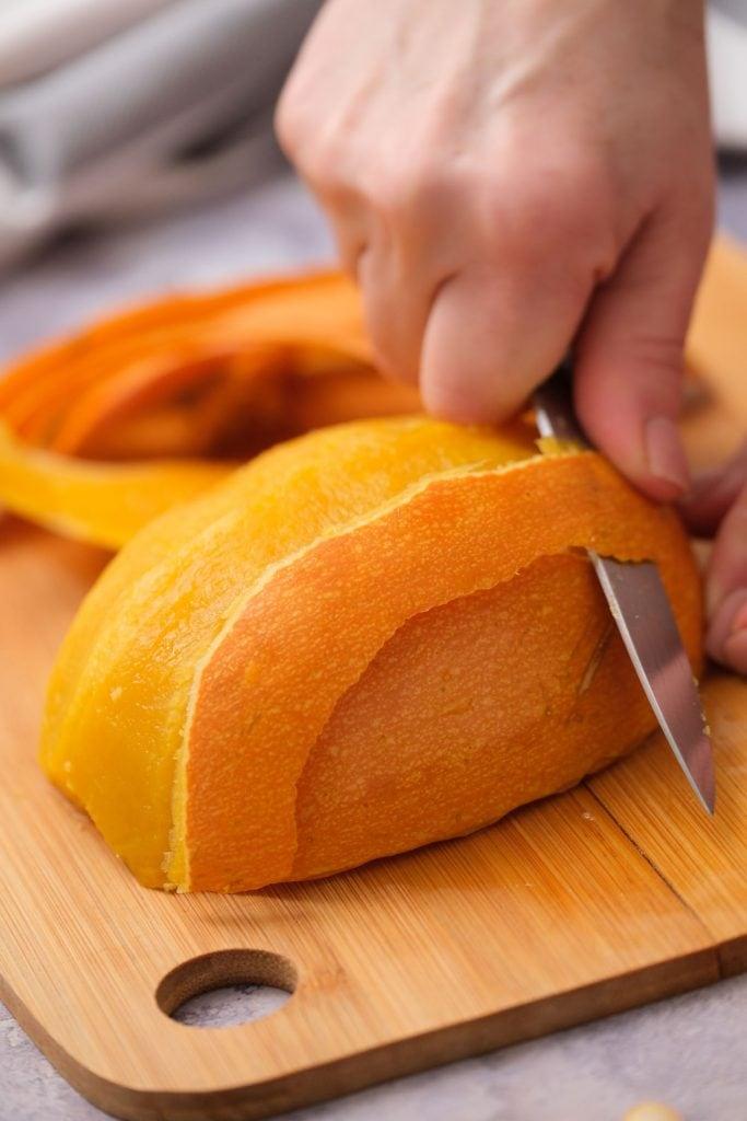 pumpkin skin being cut off of pumpkin