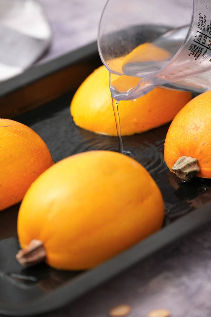 water being poured into shallow baking dish with pumpkins