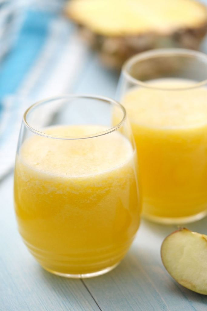 pineapple apple juice in glass cups on blue table