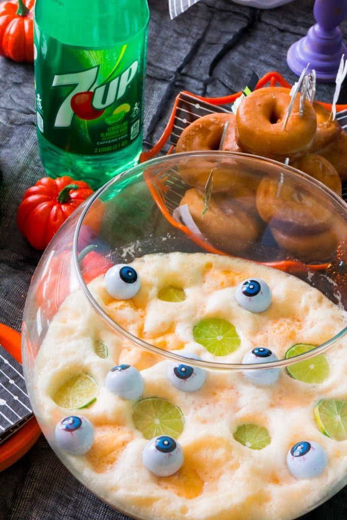 halloween punch in glass bowl on top of black table cloth with 7up bottle behind it