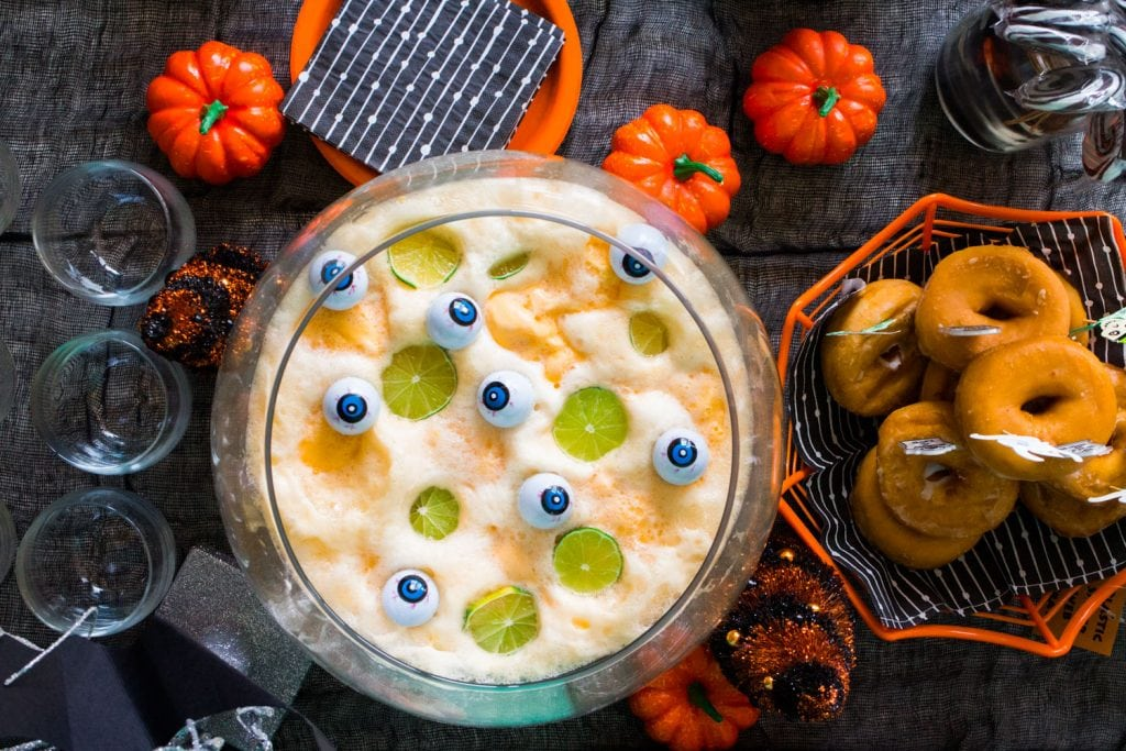 halloween tablescape with punch bowl, donuts and decorations
