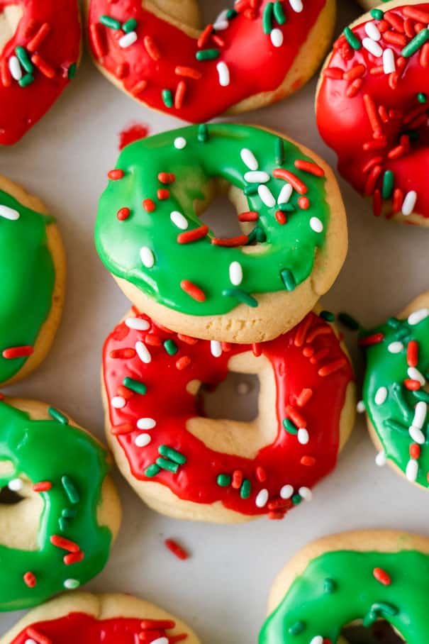 Easy to make Christmas Donut Cookies recipe.   Each sugar cookie is decorated with icing and sprinkles to look like a donut.  If you're looking for the cutest homemade Christmas co