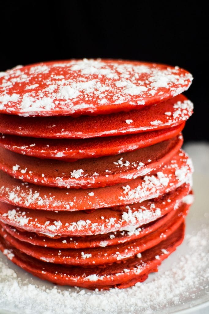 red gingerbread pancakes with powdered sugar on them