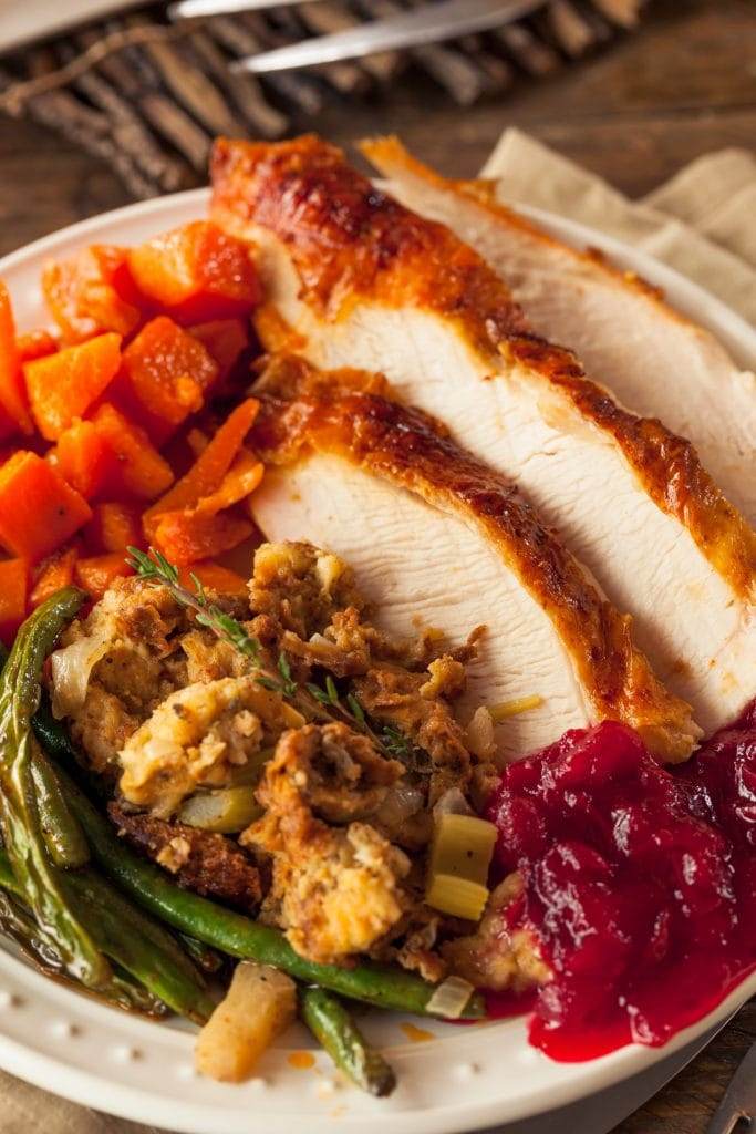 slices of juicy turkey on plate next to thanksgiving side dishes, stuffing, green beans, carrots and cranberries.