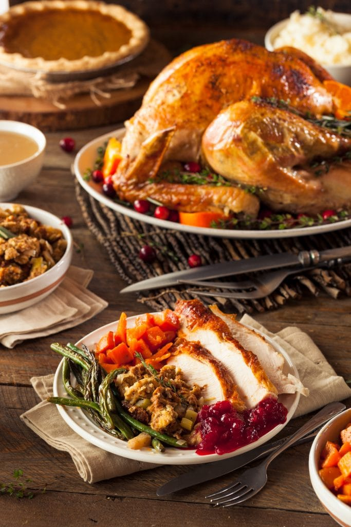 table filled with thanksgiving dinner, a whole turkey and side dishes.