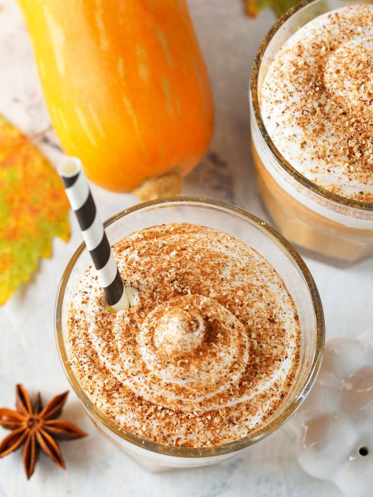 pumpkin pie milkshake with cinnamon and whipped cream on top on white table.