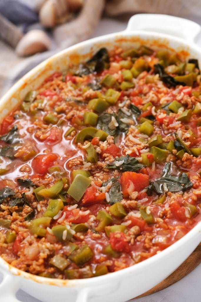 oven baked stuffed pepper casserole straight out of the oven on white table.