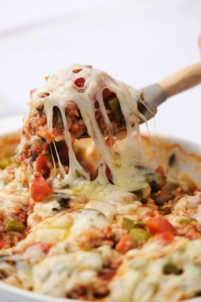 stuffed pepper casserole on spoon being lived from casserole dish.