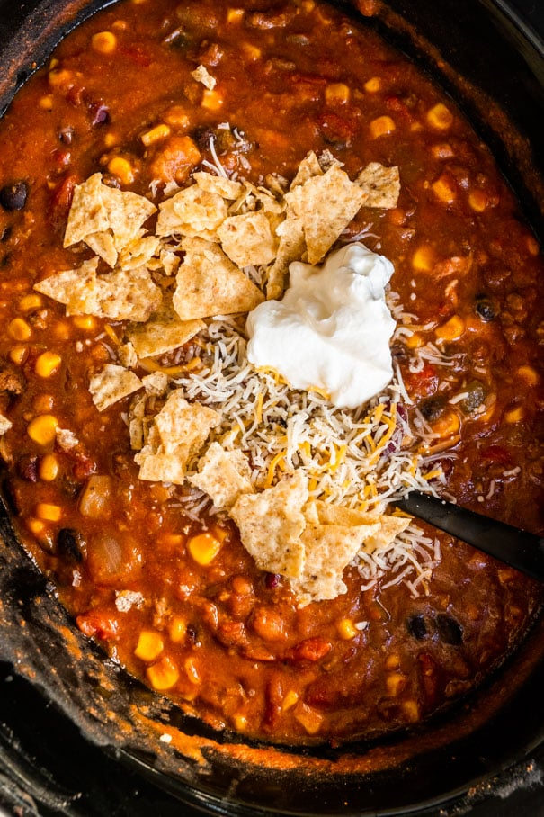 Easy Slow Cooker Taco Soup recipe, made in the crockpot with ground beef and 8 cans. This creamy soup is ready in 4 hours on high or 8 hours on low.