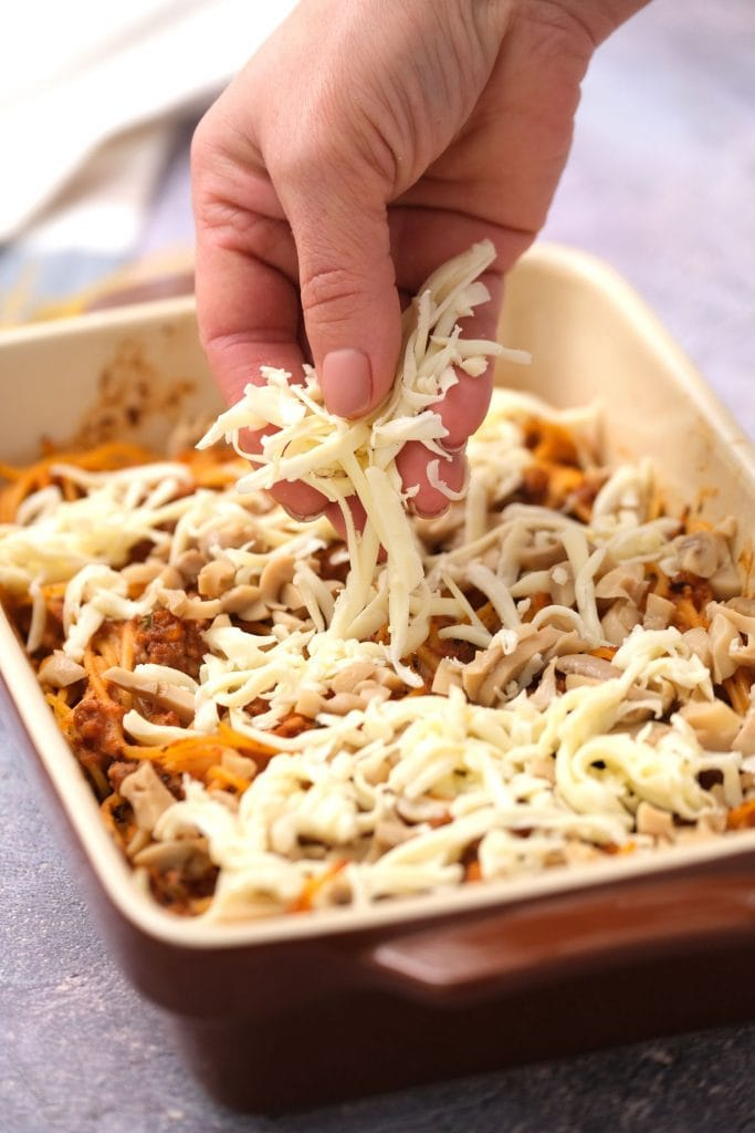 shredded mozzarella cheese being added on top of casserole
