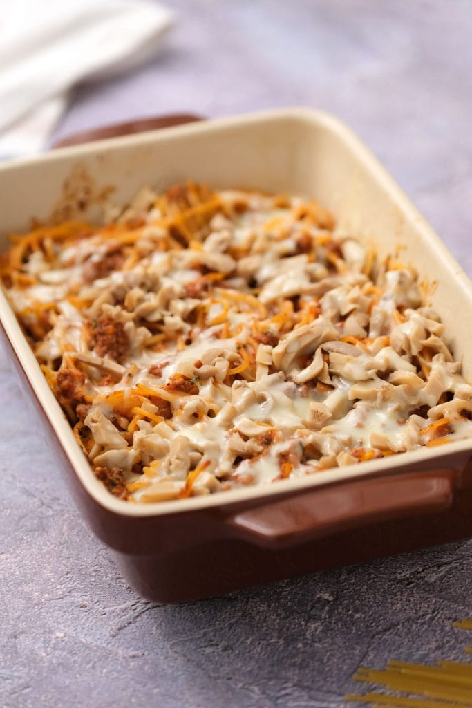 baked spaghetti casserole with melted cheese in red baking dish