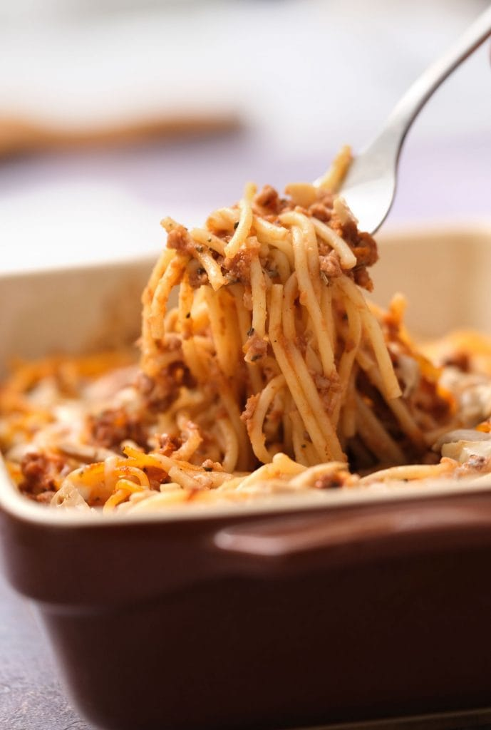 spaghetti casserole being picked up and served with fork