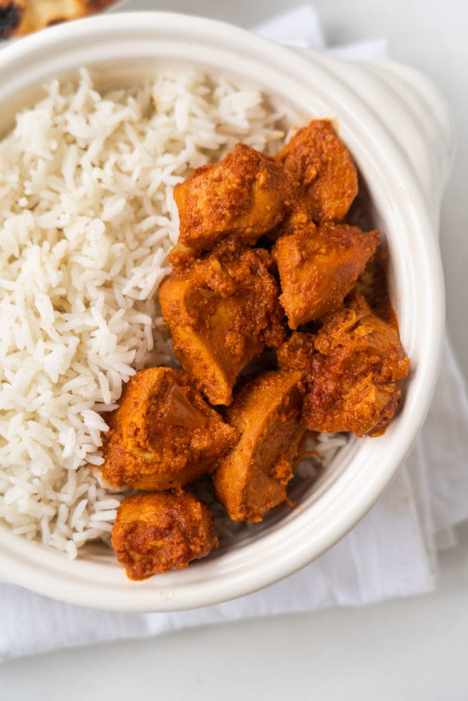 butter chicken and basmati rice in bowl.