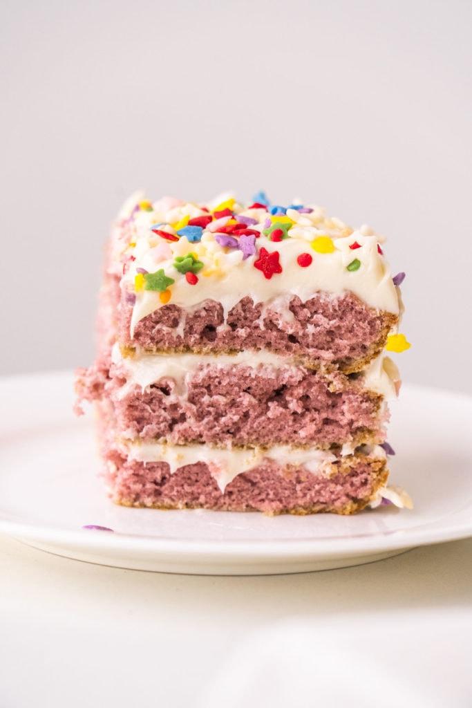 3 layer birthday cake with vanilla frosting on white cake