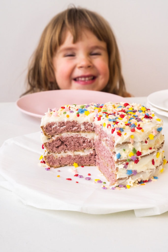 little girl smiling next to purple birthday cake with sprinkles