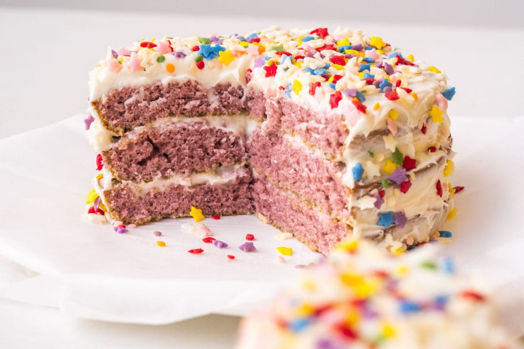 small birthday cake with vanilla frosting and rainbow sprinkles on white plate