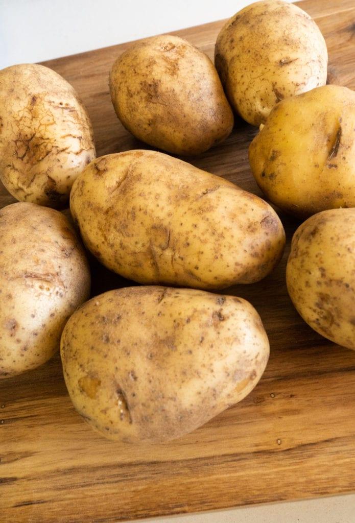 fresh potatoes on cutting board