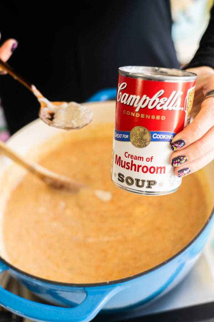 cream of mushroom soup being added in pot of soup