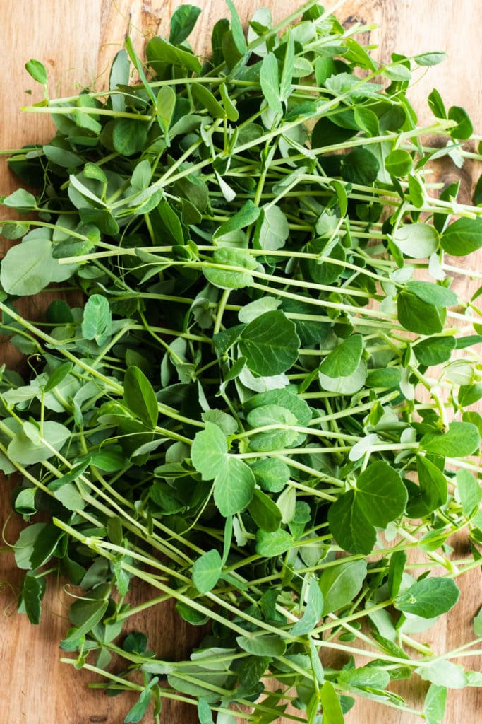 fresh pea shoots on cutting board