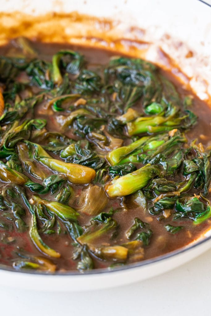 bok choy with brown sauce in white skillet