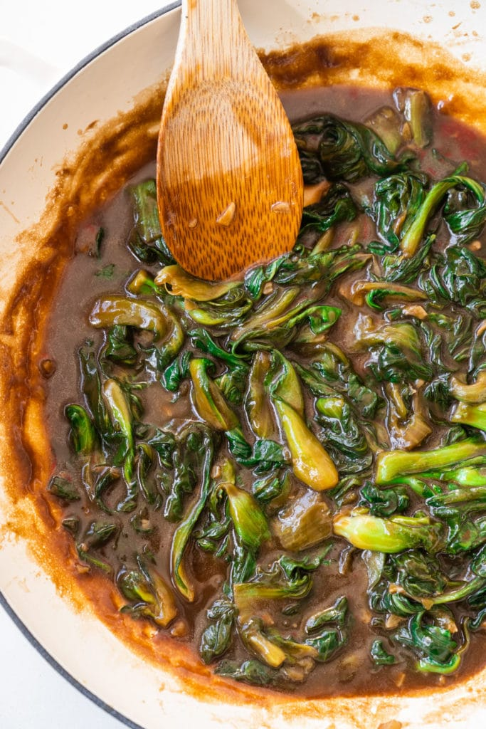 bok choy in skillet with wooden spin